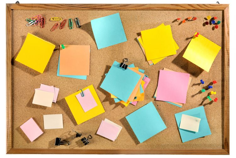 Editable blank post-its and office supplies on message board.